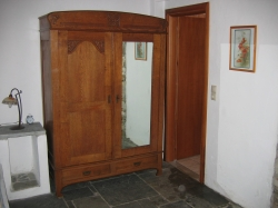 a cupboard from the early 19th century with a mirrored door.