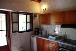 kitchen with fridge, oven with three hobs and single bed.